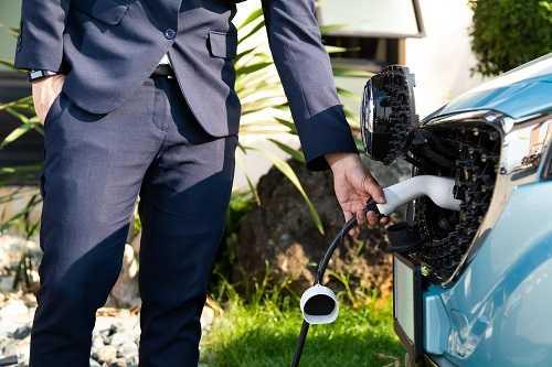 איש עסקים עם חליפה מטעין רכב חשמלי